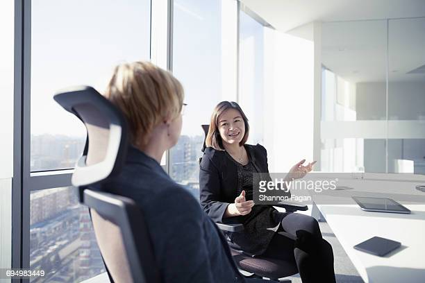 Business women talking together in meeting room