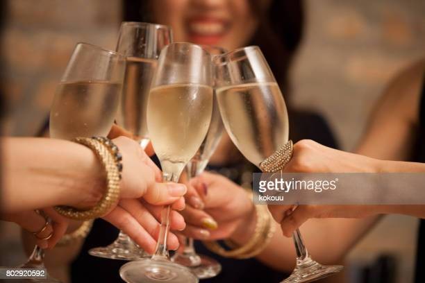 business women toast with a glass of wine in hand. - champagne stock pictures, royalty-free photos & images
