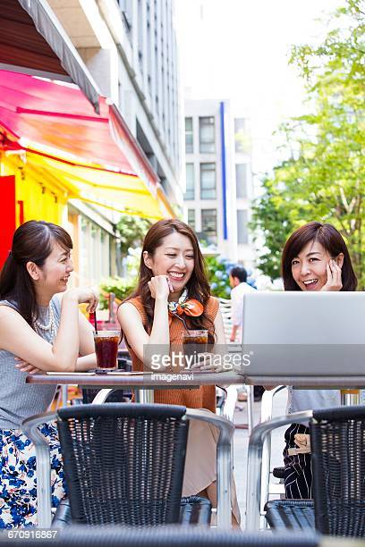 Business women using a computer at an outdoor cafe