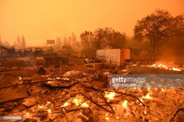 Businesses continue to burn under a darkened smokey sky in Paradise, north of Sacramento, California on November 09, 2018. - A rapidly spreading,...