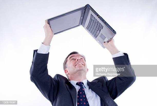businessman, 50+, holding a laptop above his head - michaela du toit photos et images de collection