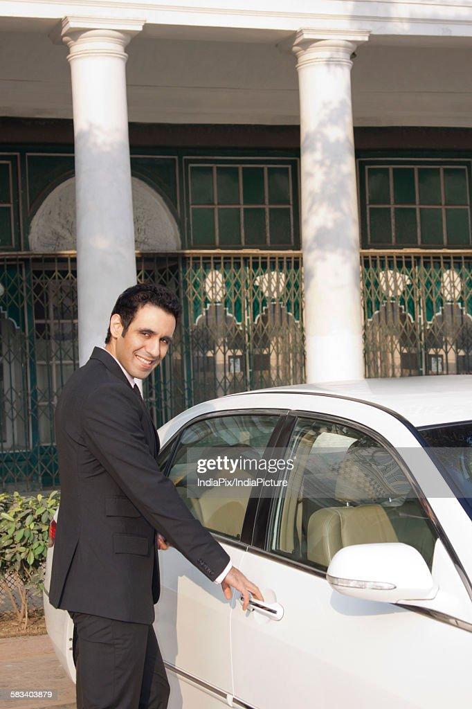 Businessman about to open car door , INDIA , DELHI : Stock Photo