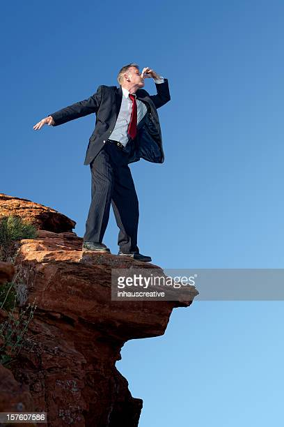 Businessman About To Plung Over The Edge