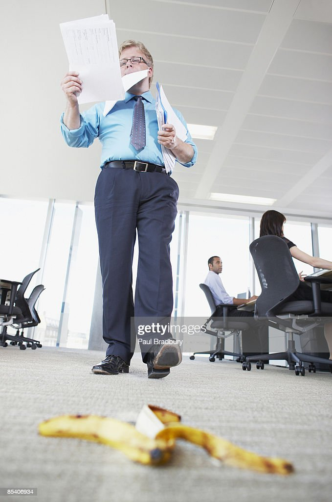 Businessman about to step on banana peel : Stock Photo
