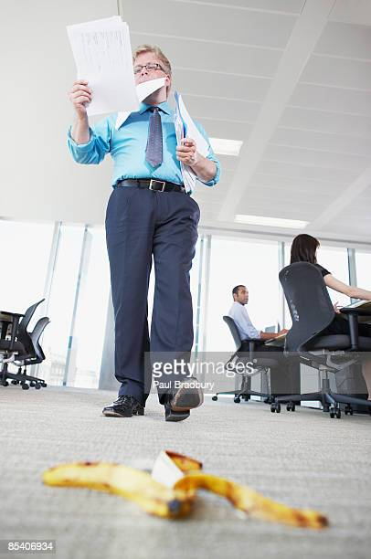 Businessman about to step on banana peel