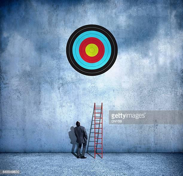 Hombre de negocios sobre el uso de escalera para alcanzar el objetivo.