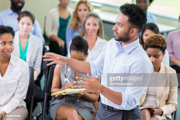 businessman addresses the crowd during a seminar - town hall stock pictures, royalty-free photos & images