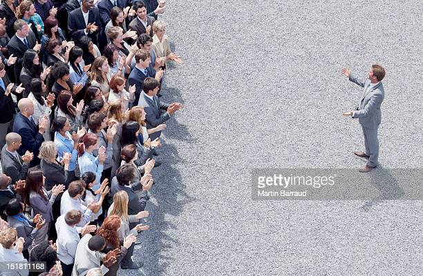 businessman addressing clapping crowd - politician stock pictures, royalty-free photos & images