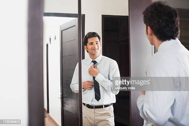 Businessman adjusting his necktie in front of a mirror