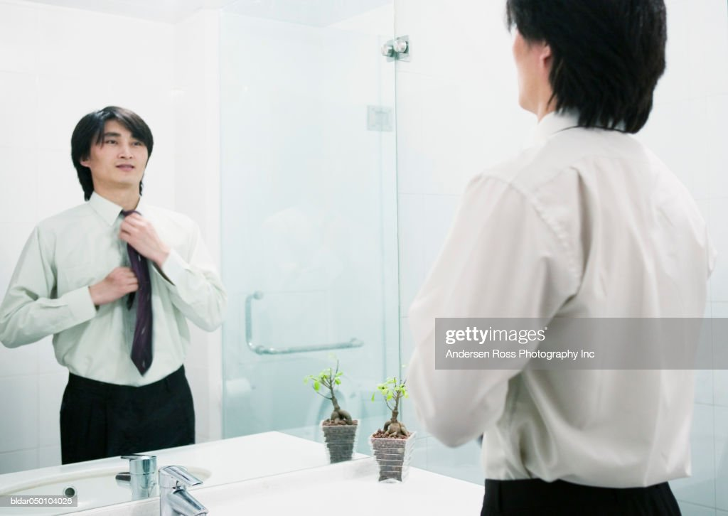 Businessman adjusting his tie in a mirror, Beijing, China : Stock Photo