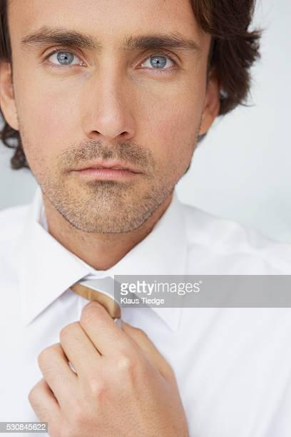 Businessman adjusting necktie