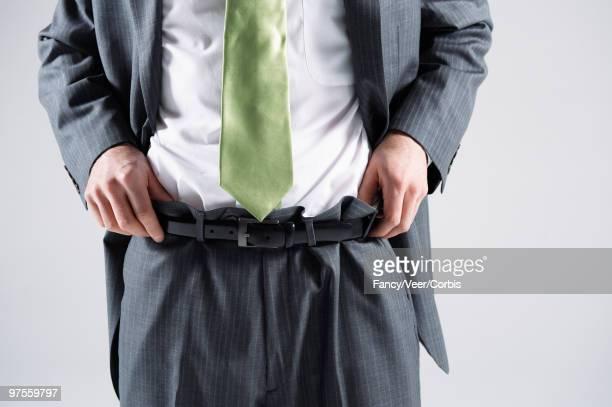 Businessman adjusting pants