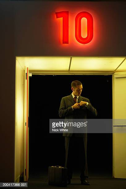Businessman adjusting suit by door under neon '10' sign