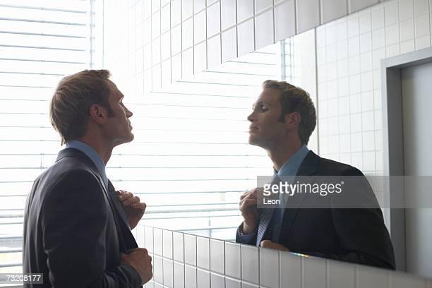 Businessman adjusting tie in bathroom mirror