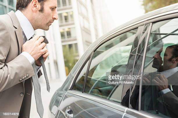 Businessman adjusting tie in car window