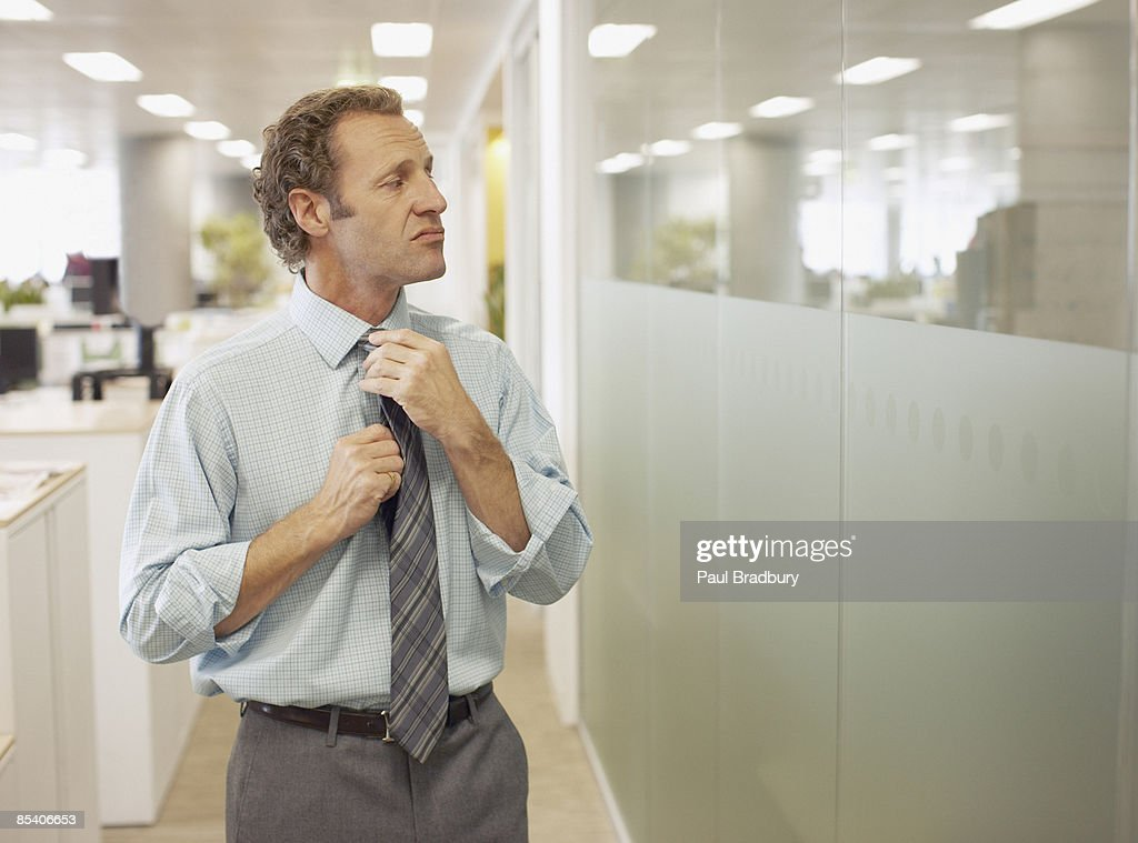 Businessman adjusting tie in office : Stock Photo