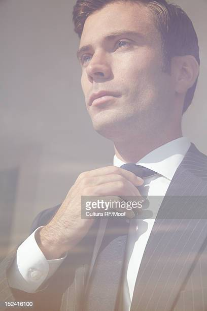 Businessman adjusting tie in window