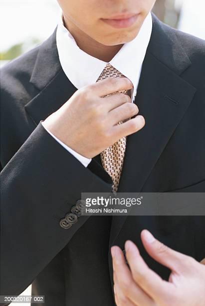 Businessman adjusting tie, mid section