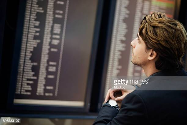 Businessman adjusting wrist watch while reading arrival departure board at airport