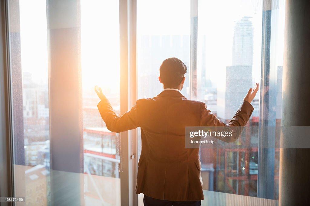 Businessman admiring city through window as the sun sets : Stock Photo