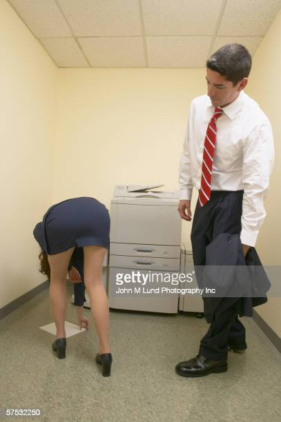 Businessman admiring female colleague?s buttocks as she bends over
