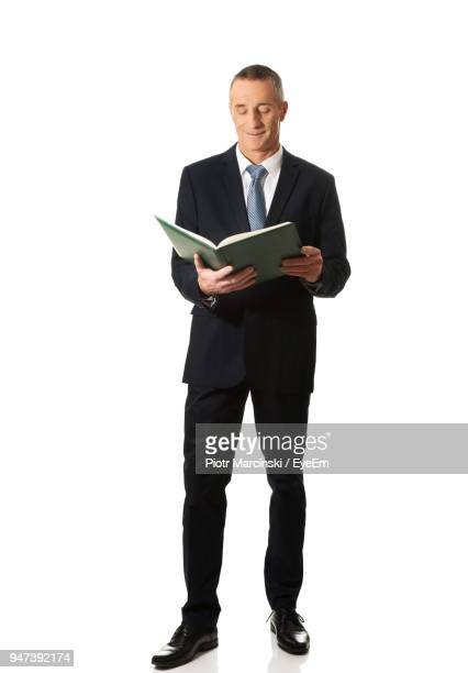 businessman against white background - man holding book stock pictures, royalty-free photos & images