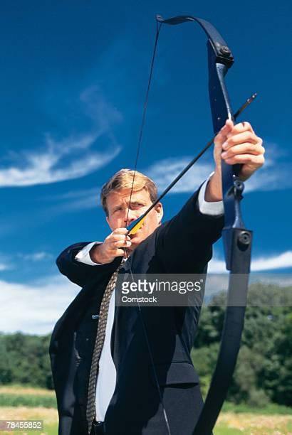 Businessman aiming archery bow