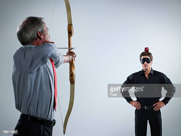 Businessman Aiming at an Apple on a Man's Head