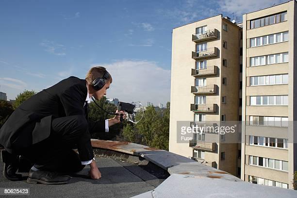 Businessman Aiming Audio Surveillance Equipment into Apartment Building