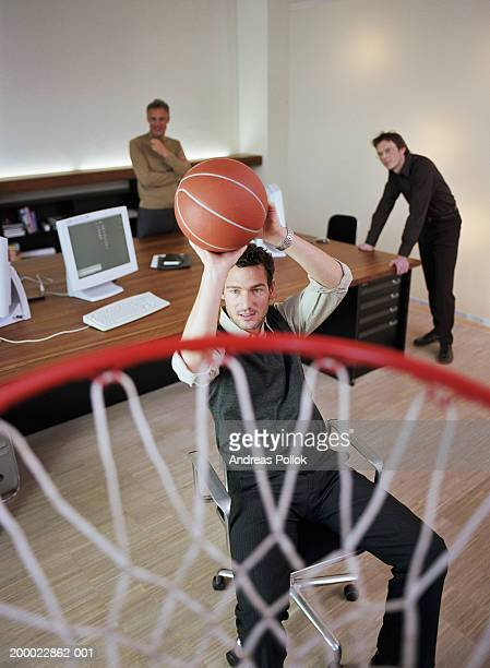 Businessman aiming to shoot basketball in office, elevated view