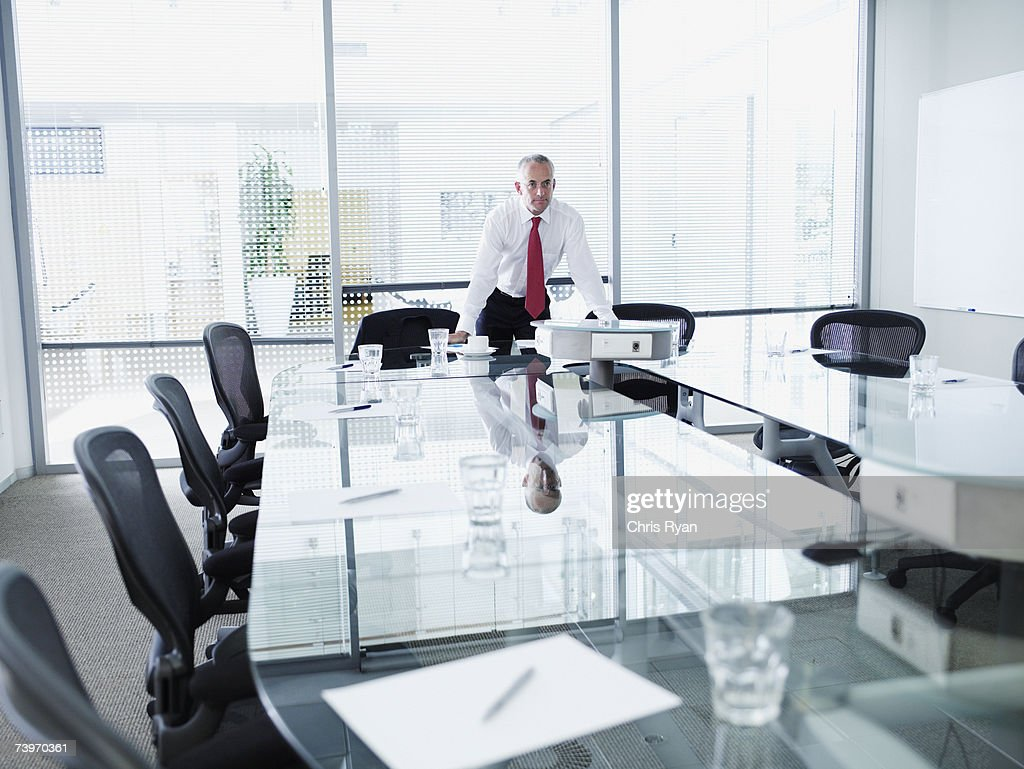 Businessman alone in a boardroom leaning on table : Stock Photo