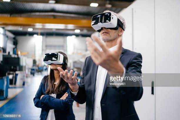 businessman an woman in high tech enterprise, using vr glasses - simulatore di realtà virtuale foto e immagini stock