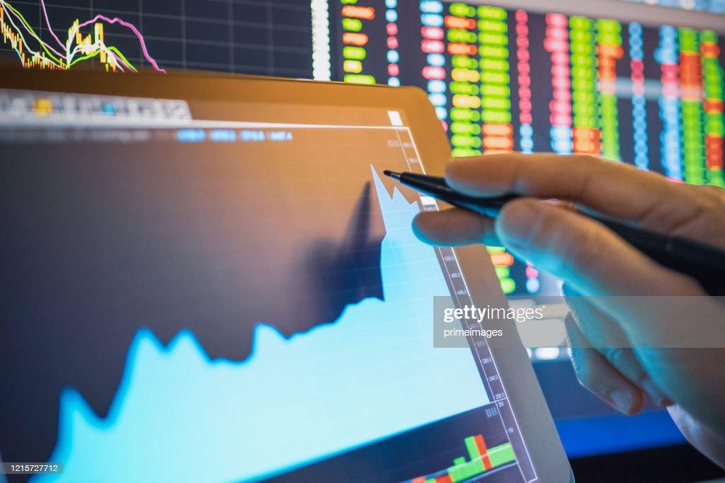 Gráfico de ações de análise de empresários em crise covid-19 para investimento em bolsa de valores e finanças planejamento de ações seletivas para a queda da bolsa e crise financeira : Foto de stock