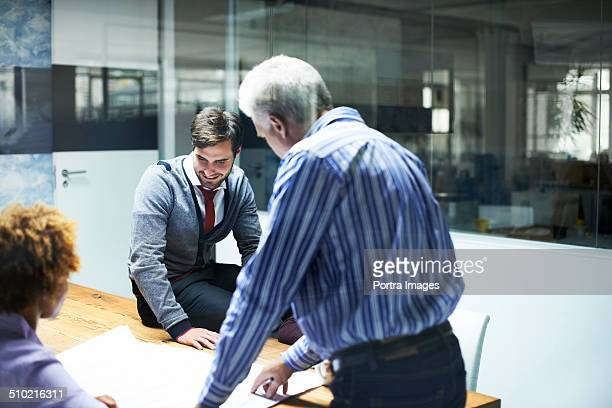 Businessman analyzing blueprint with colleagues