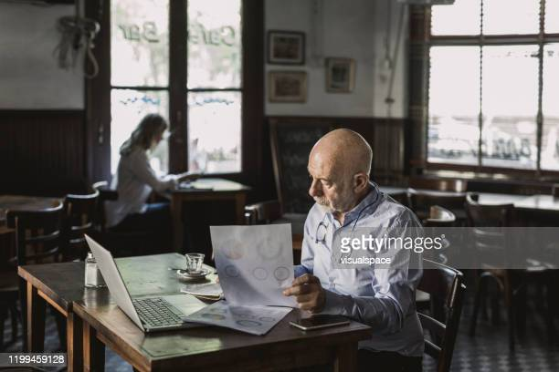 businessman analyzing data - working seniors stock pictures, royalty-free photos & images