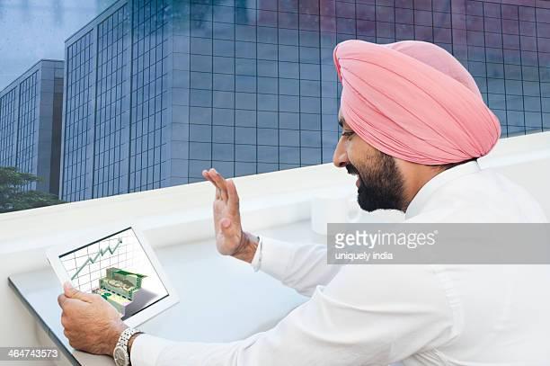 Businessman analyzing graph on a digital tablet