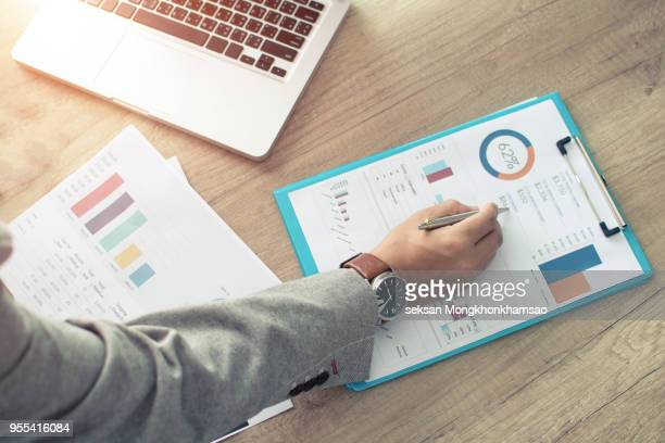 businessman analyzing investment charts. accounting - ganar dinero fotografías e imágenes de stock