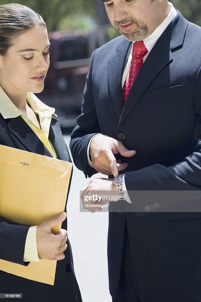 Businessman and a businesswoman checking the time in a wristwatch : Stock Photo