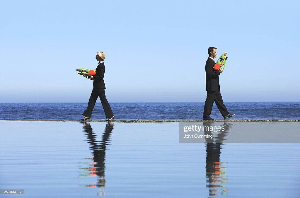 Businessman and a Businesswoman Dueling With Water Pistols by the Sea : Stock Photo