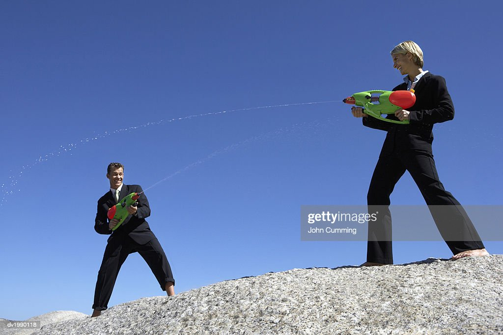 Businessman and a Businesswoman Dueling With Water Pistols : Stock Photo