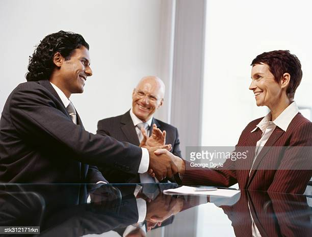 businessman and a businesswoman shaking hands in an office