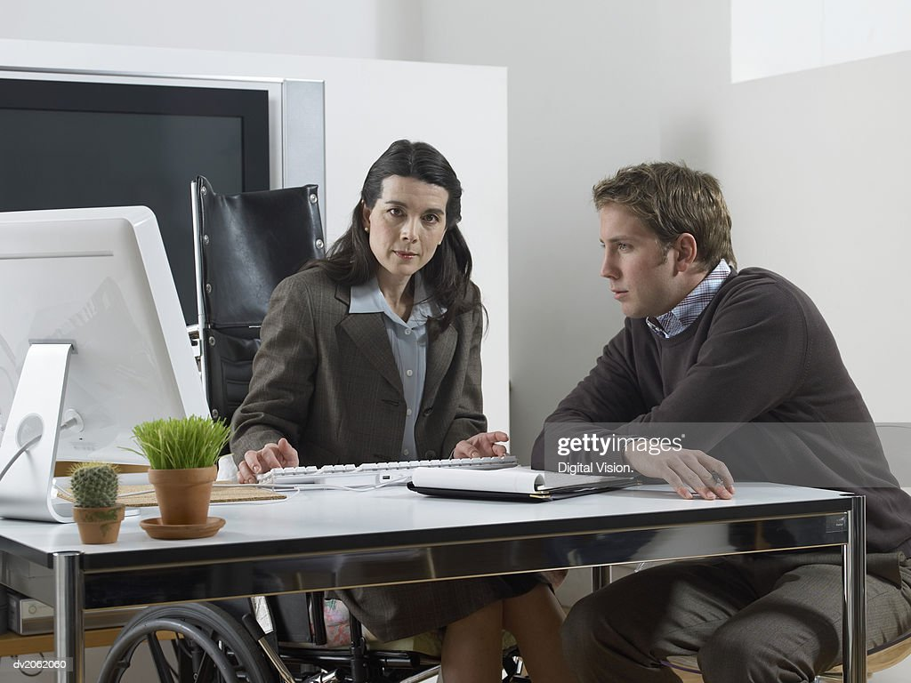 Businessman and a Businesswoman Sitting at a table, Woman in a Wheelchair : Stock Photo