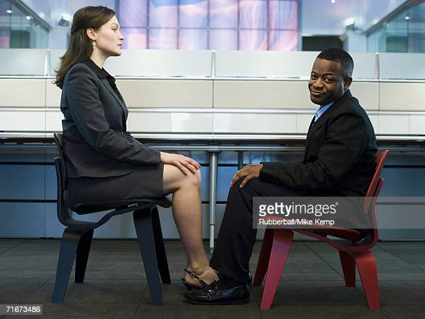 Businessman and a businesswoman sitting face to face