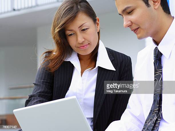 businessman and a businesswoman sitting together and using a laptop - nepalese ethnicity stock pictures, royalty-free photos & images