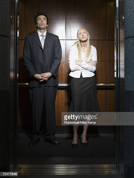 businessman and a businesswoman standing in an elevator - embrasser stock pictures, royalty-free photos & images