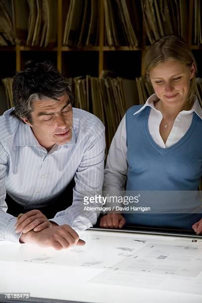 A businessman and a businesswoman standing over a light box