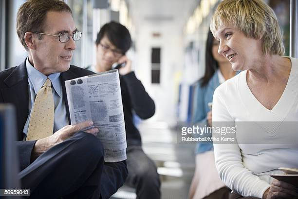Businessman and a businesswoman talking on a commuter train