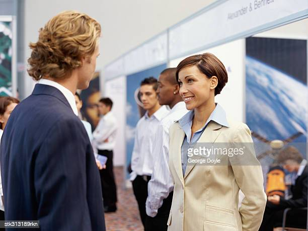businessman and a businesswoman talking to each other at an exhibition - tradeshow stock pictures, royalty-free photos & images