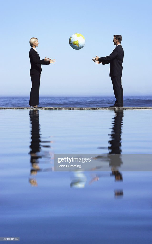 Businessman and a Businesswoman Throwing a Sphere by the Sea : Stock Photo