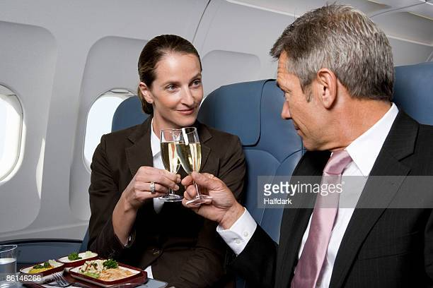 A businessman and a businesswoman toasting champagne glasses on a plane